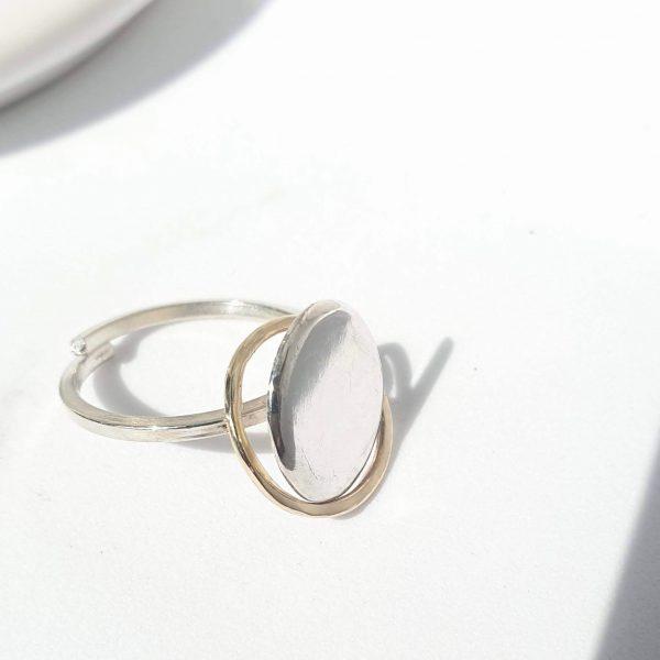 Bague en argent massif. Pièce d'argent façonnée dans l'atelier et anneau en or 14kt qui gravite autour de la pièce.